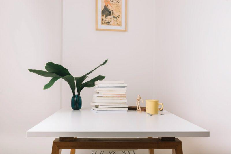 biely stôl s rastlinou a knihami