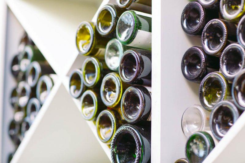 fľaše od vína uložené v regáloch